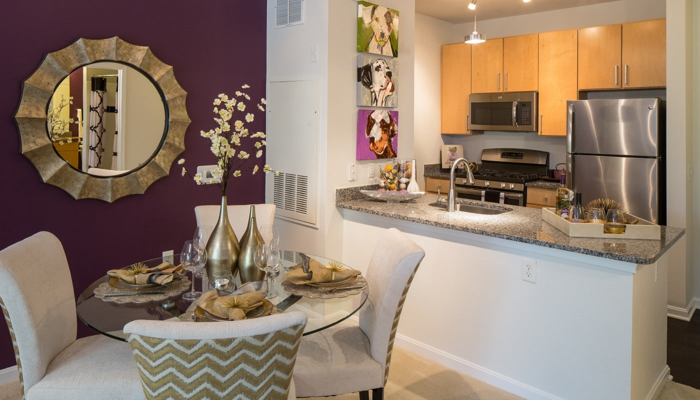 congressional village kitchen and dining area with granite countertops, stainless steel appliances, table, four chairs, place settings, large mirror and modern artwork - jefferson apartment group