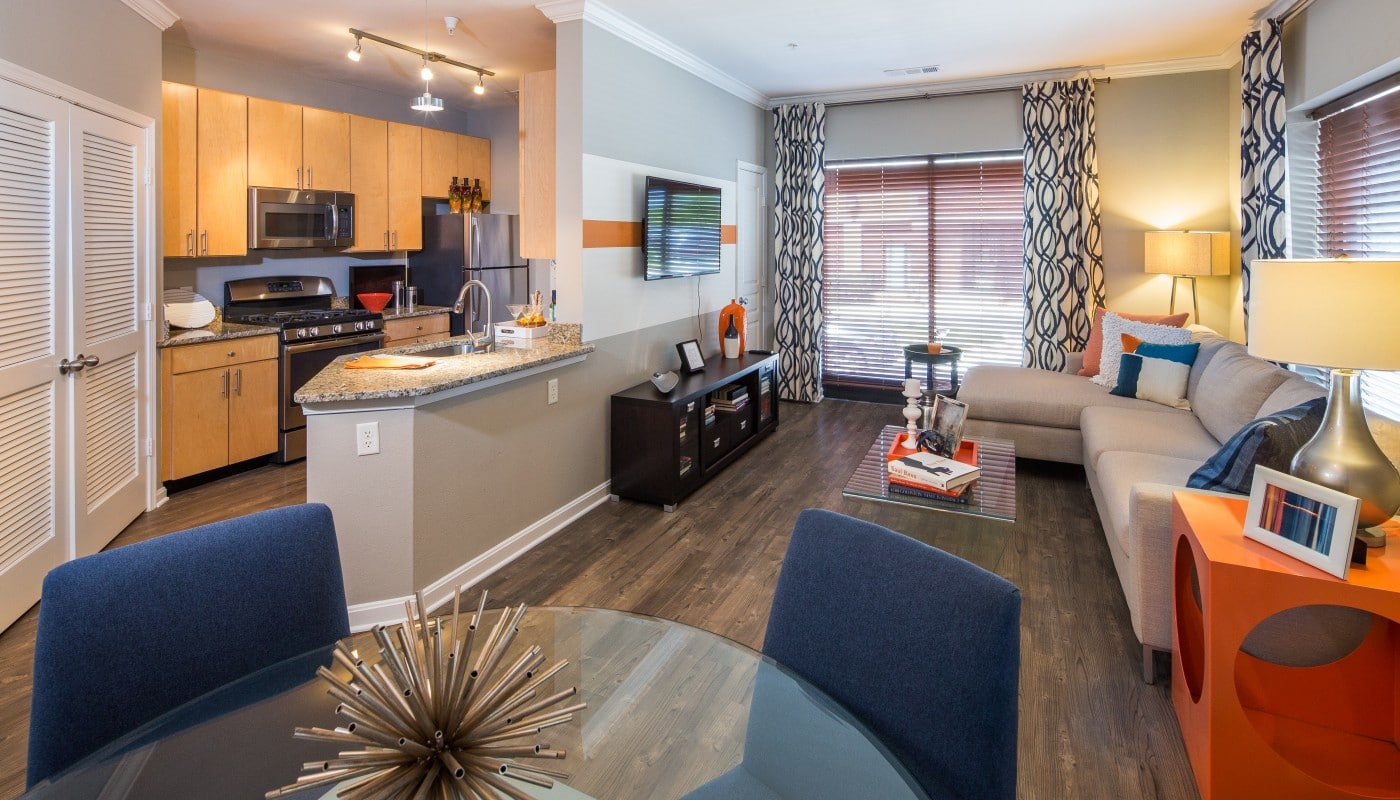 congressional village living area with sectional sofa, coffee table, end table, dining area and view of kitchen with granite countertops, statinless steel appliances and plank flooring throughout - jefferson apartment group
