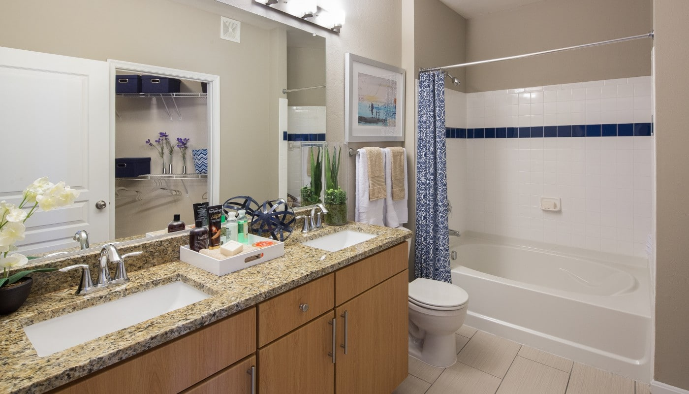congressional village bathroom with garden but, granite vanity with double sinks, tiled flooring, large mirror and view of walk in closet - jefferson apartment group
