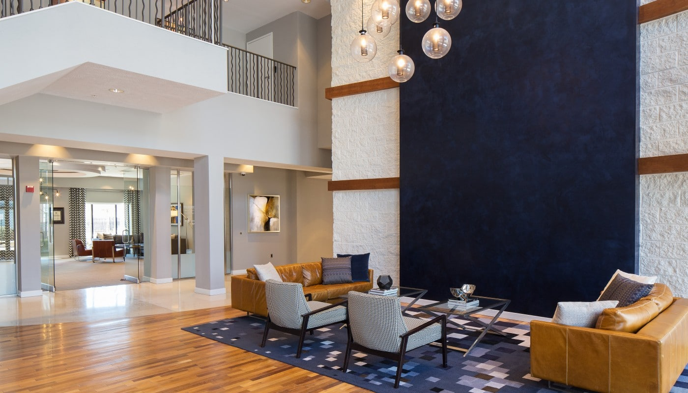 congressional village resident lounge with leather sofas, side chairs, cocktail tables, modern lighting and view of leasing office - jefferson apartment group