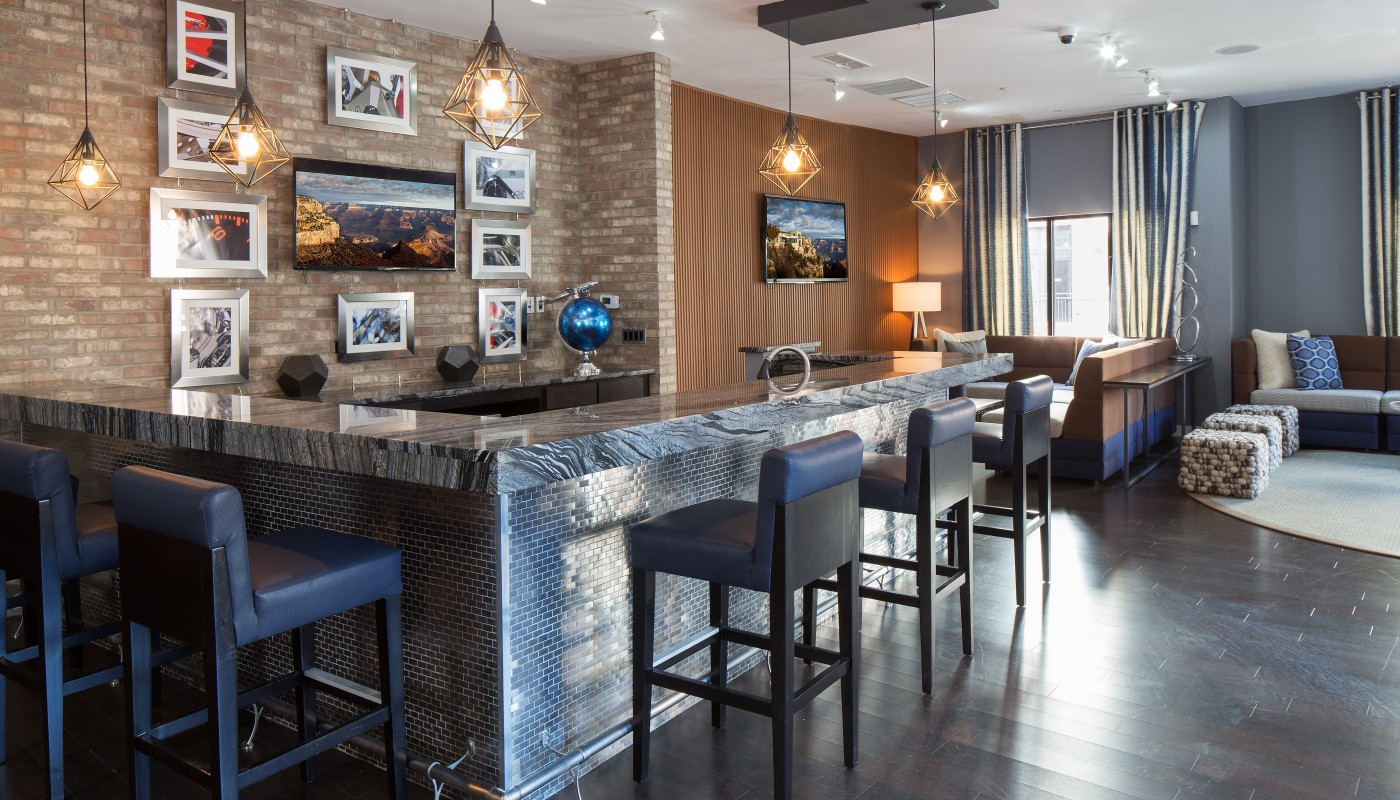 congressional village club room with bar seating, flat screen tv, socil seating, cocktail tables and modern artowork and lighting - jefferson apartment group