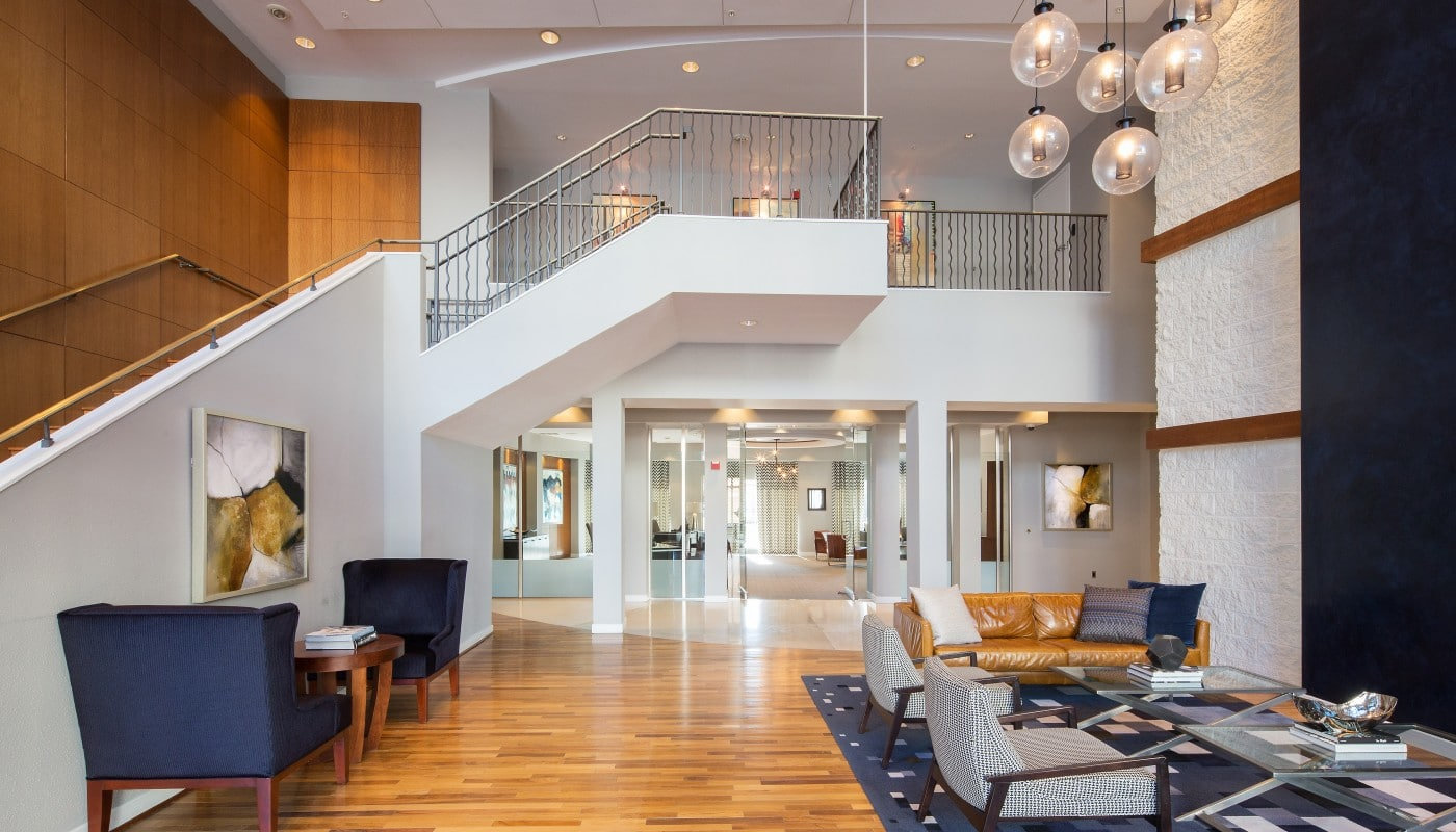 congressional village lobby with tables, chairs, social seating, grand staircase and modern lighting - jefferson apartment group