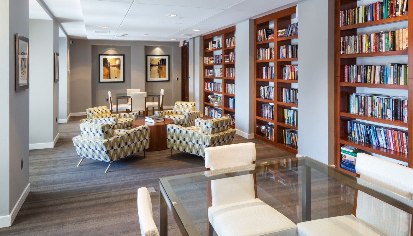 congressional village resident lounge library with bookshelves, social seating, tables and chairs - jefferson apartment group