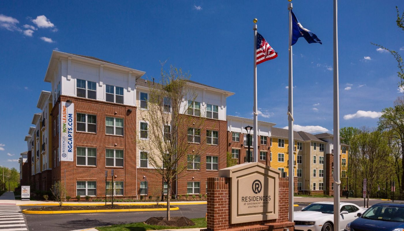 exterior of 4 story apartment building called residences at government center with monument sign and US and VA flags in fairfax va