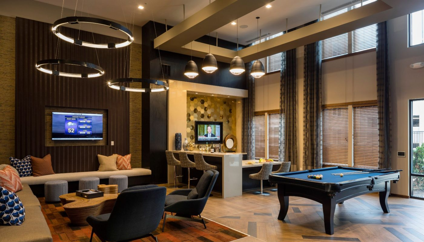 game room with social seating, billiards table and flat screen tvs at residences at government center in fairfax va