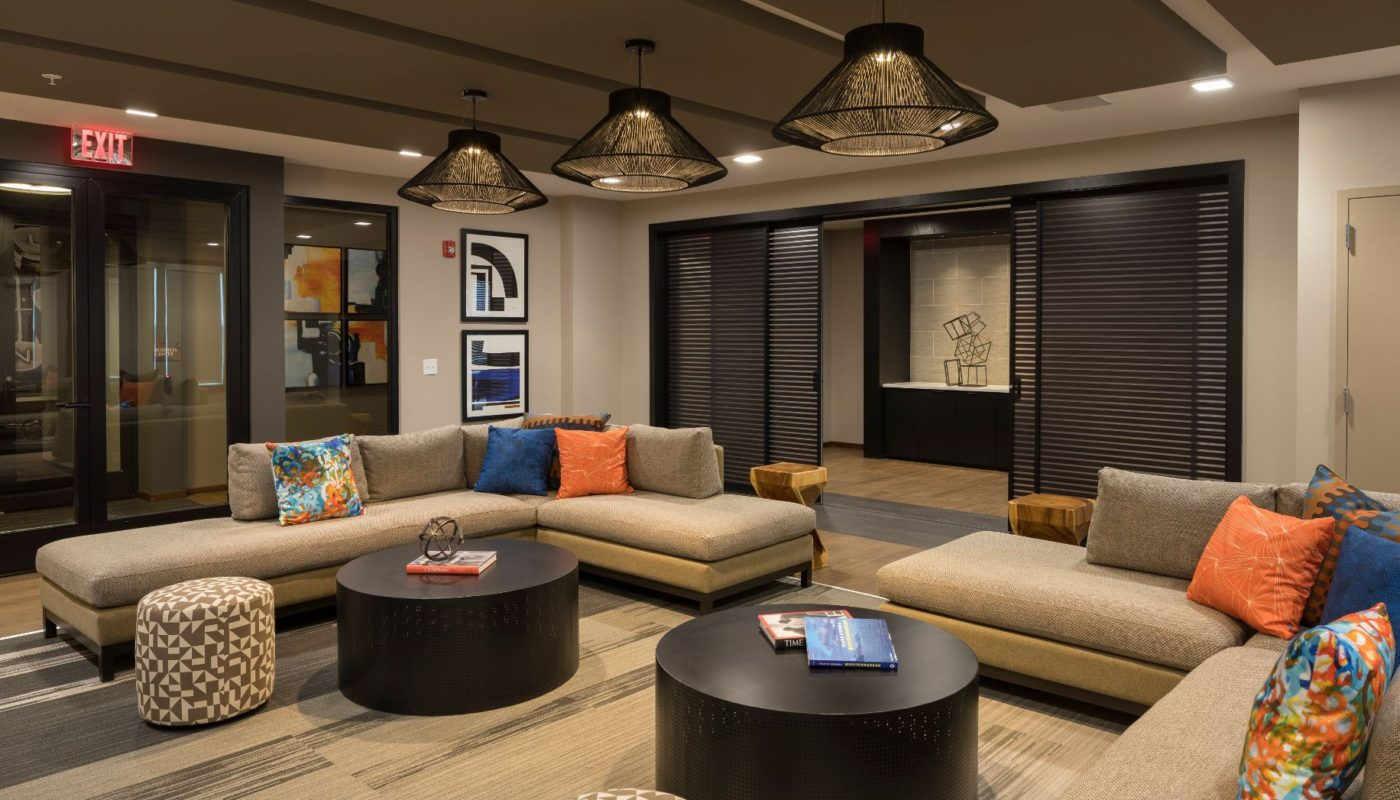 lounge at residences at government center with social seating, tables, decorative lighting and storage cabinets