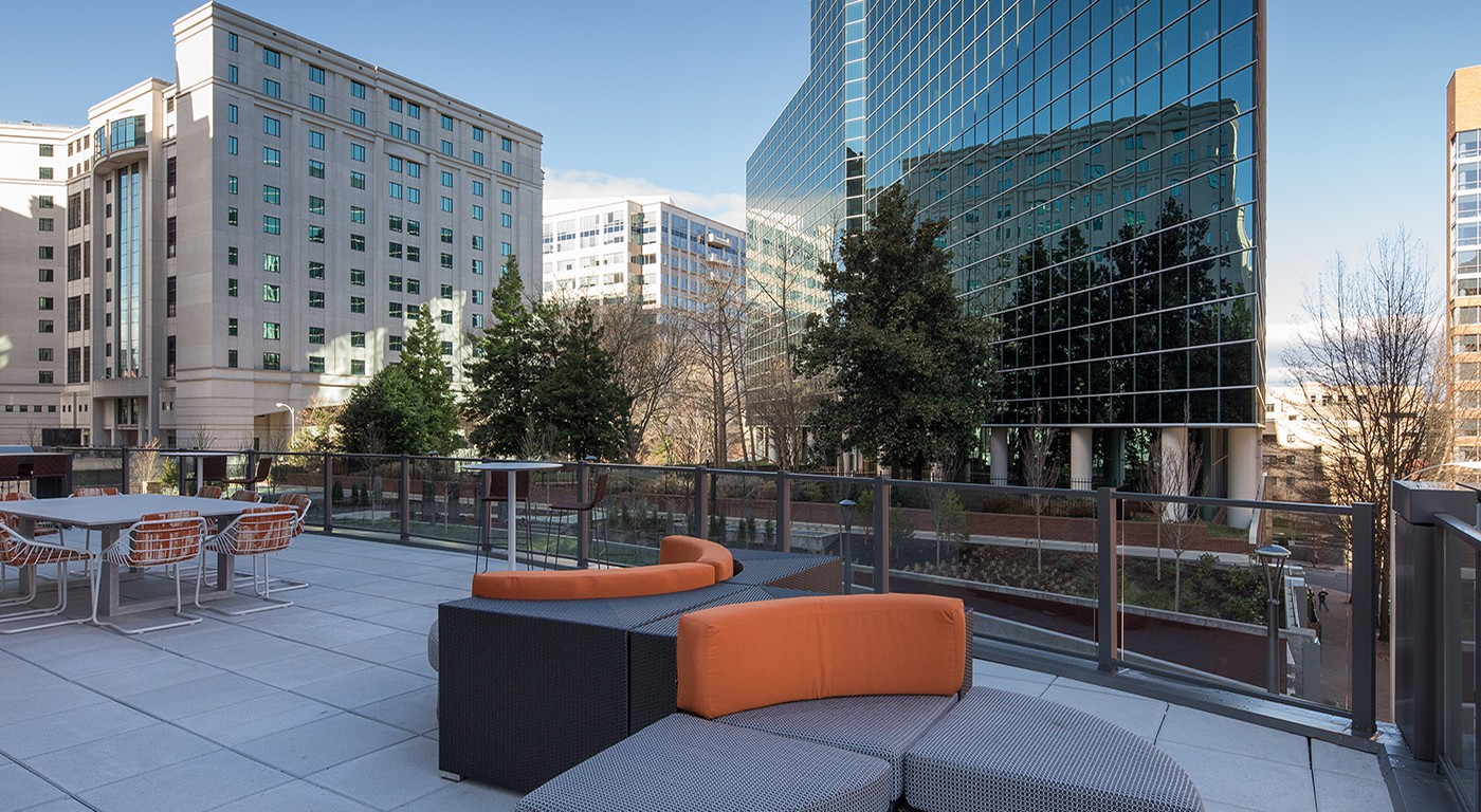 tellus resident lounge with tables, chairs, grilling area, and view of arlington - jefferson apartment group