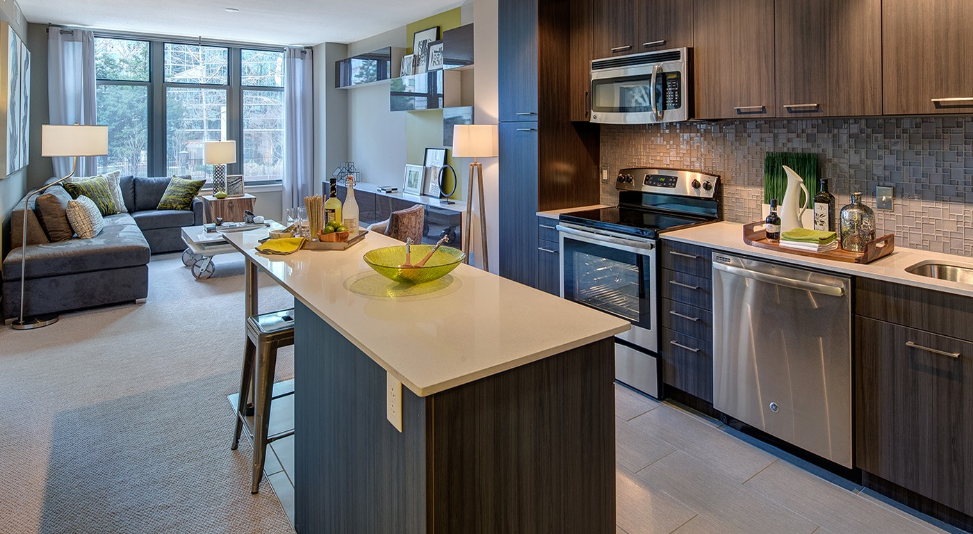 tellus kitchen with quartz countertops, stainless steel appliances, island, and view of the living area - jefferson apartment group
