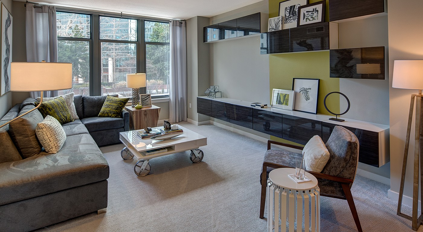 tellus living area with sectional sofa, coffee table, decorative credenza, and large window - jefferson apartment group