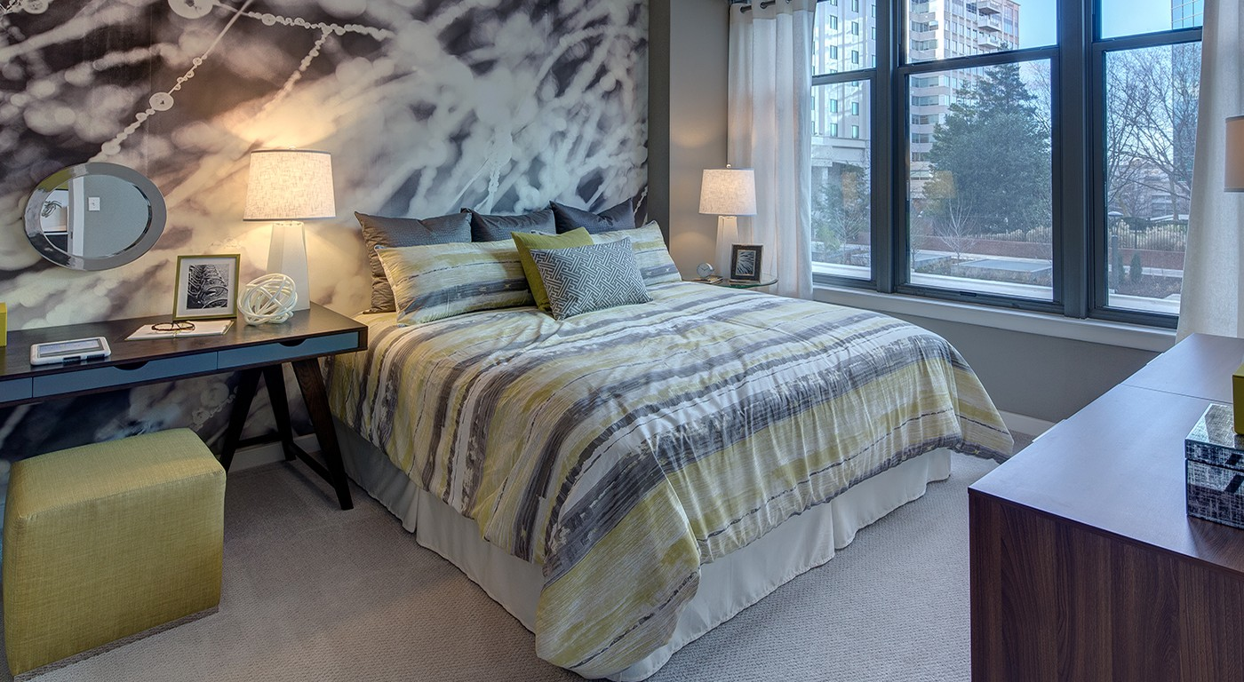 tellus bedroom with bed, desk, dresser, modern wall art, large windows and decorative lamps - jefferson apartment group