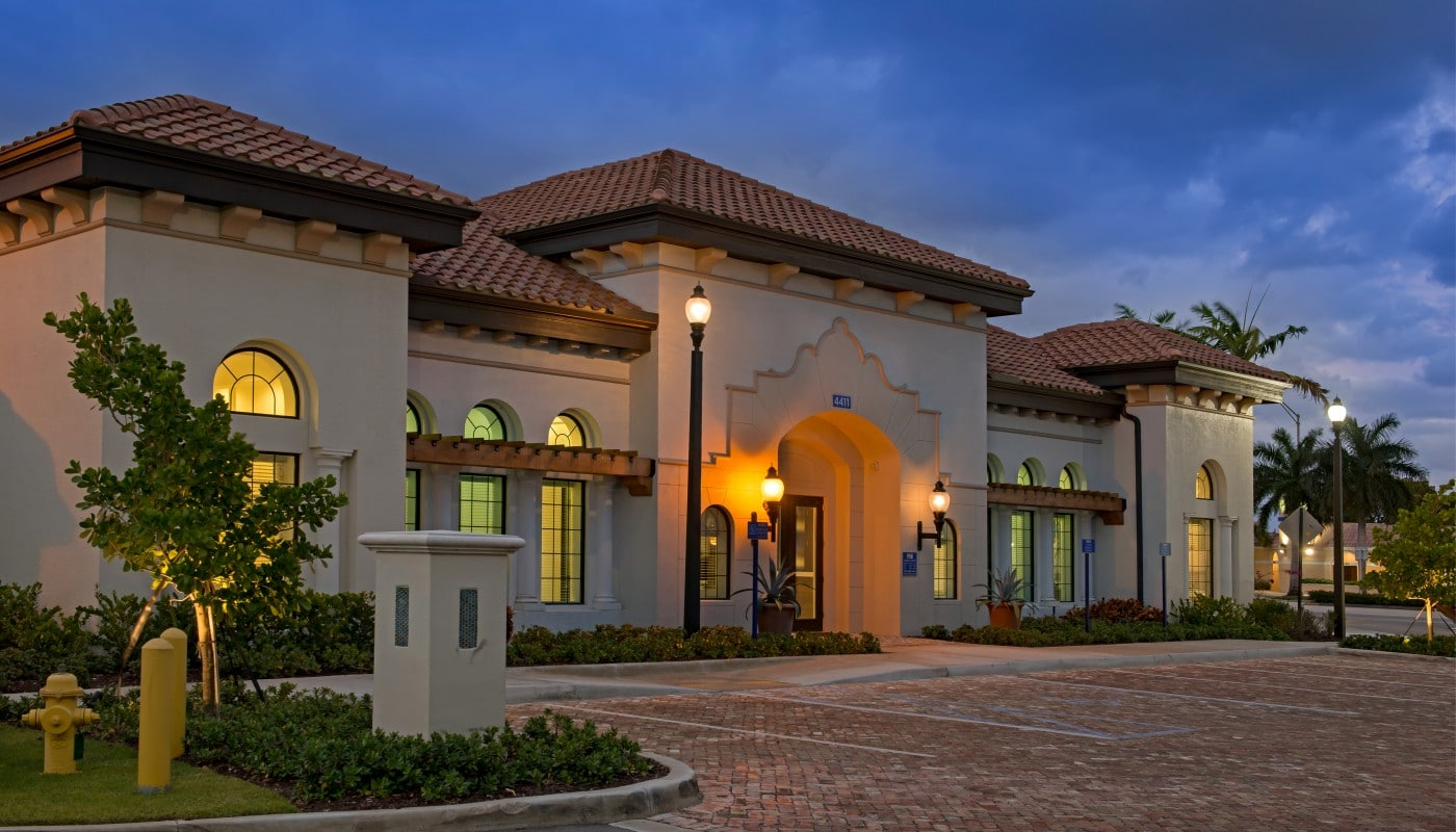 lighthouse point resident lounge exterior at night with trees, landscaping, spanish tile roof and parking area - jefferson apartment group