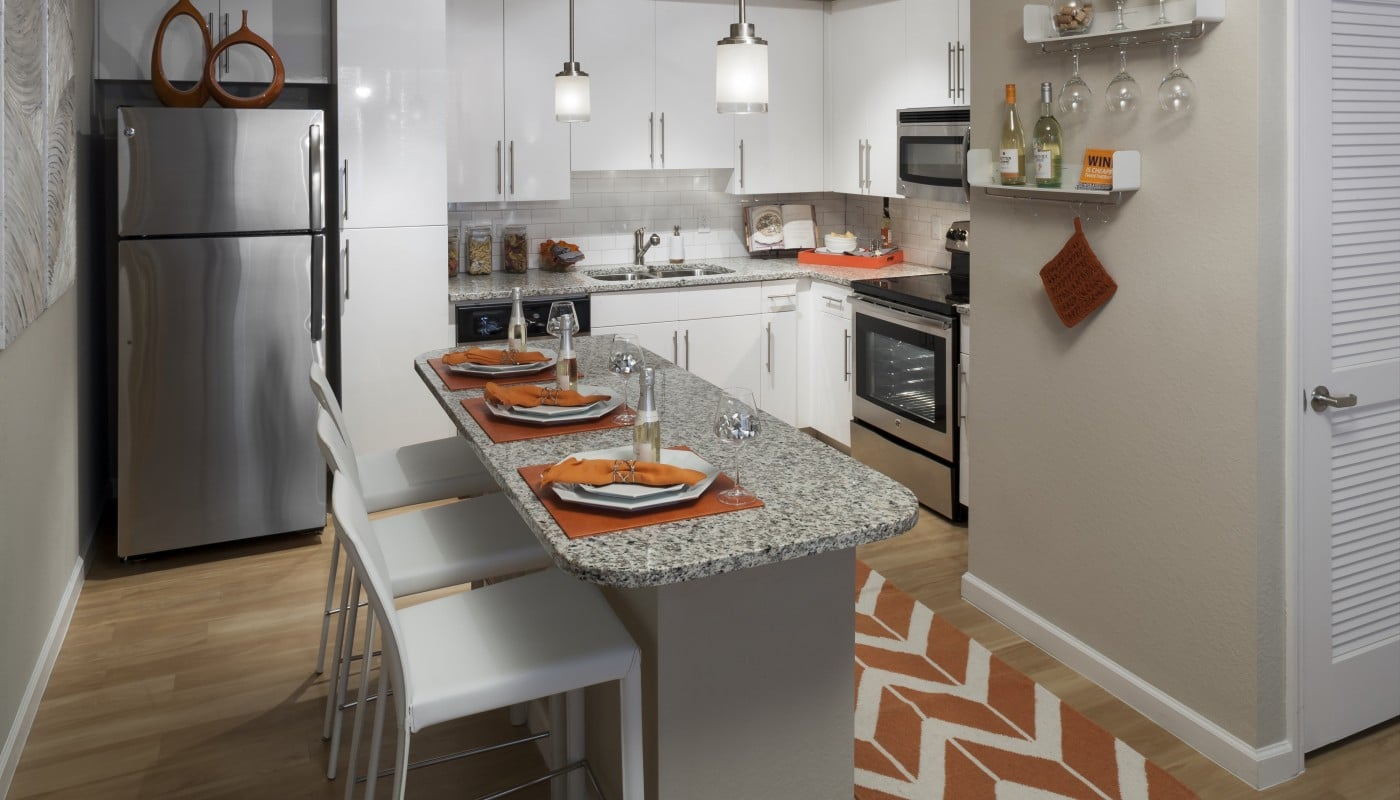 jefferson palm beach kitchen with breakfast bar, bar stools, place settings, stainless steel appliances, white cabinetry, modern lighting and plank flooring - jefferson apartment group