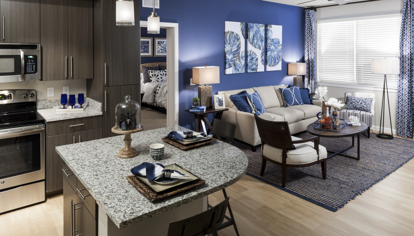jefferson palm beach living area with couch, coffee table, side chairs, blue accent wall, view of kitchen with island, stainless steel appliances, granite countertops and view of bedroom - jefferson apartment group