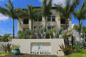 jefferson palm beach monument sign and view of apartment building and palm trees in the background - jefferson apartment group