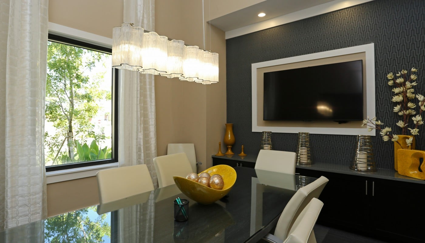 jefferson palm beach conference room with large table, chairs, storage cabinet, flat screen monitor and modern lighting - jefferson apartment group