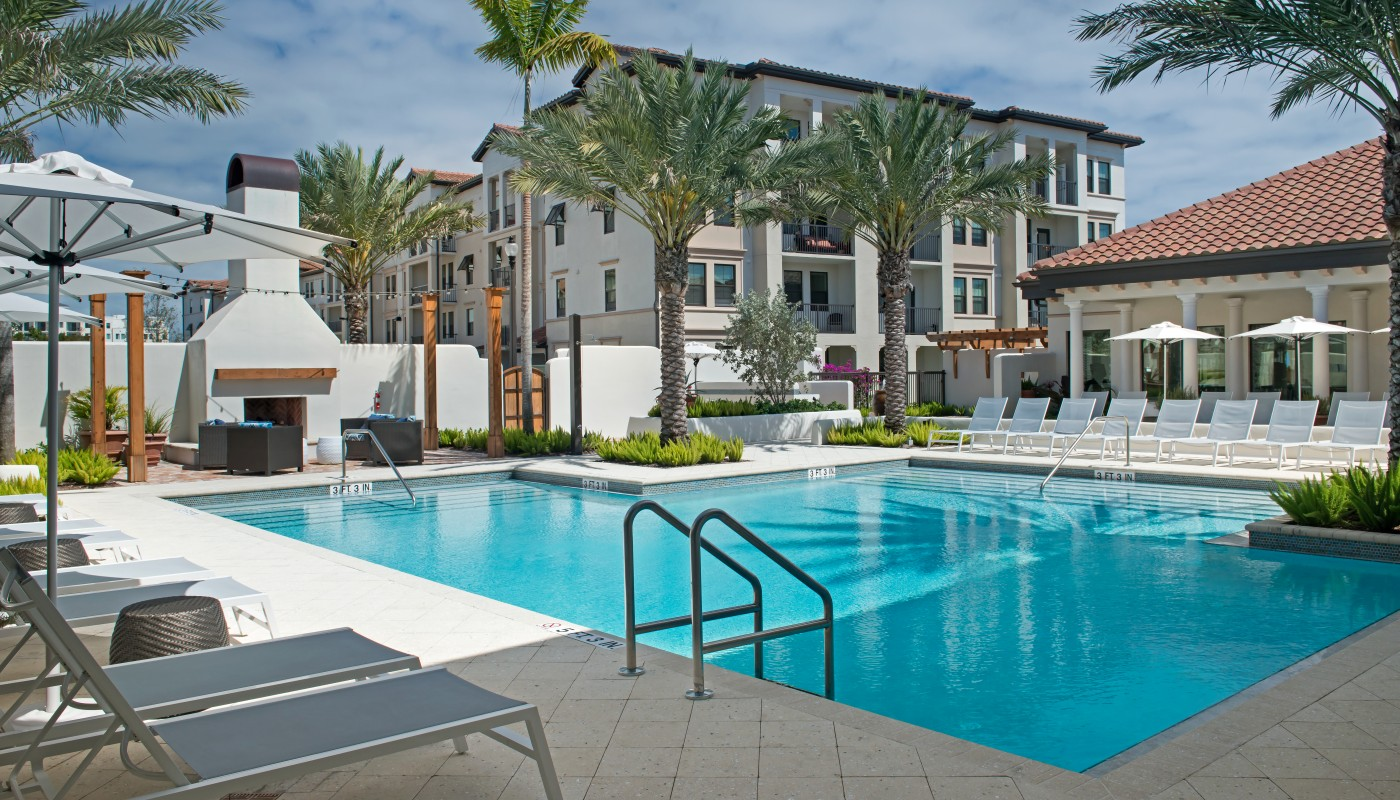 light house point resort style pool with chaise lounge chairs, umbrellas, palm frees and fireplace - jefferson apartment group