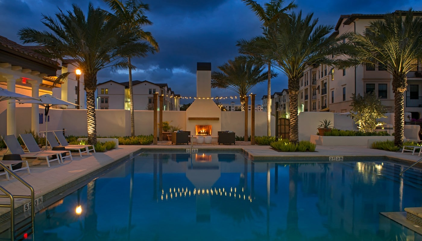 light house point resort style pool at night with chaise lounge chairs, umbrellas, palm frees and fireplace - jefferson apartment group