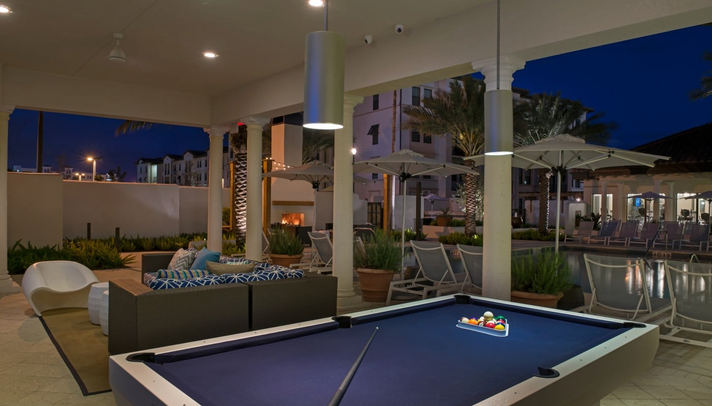 light house point outdoor game area with billiards table, social seating, and view of resort style pool and chaise lounge chairs - jefferson apartment group
