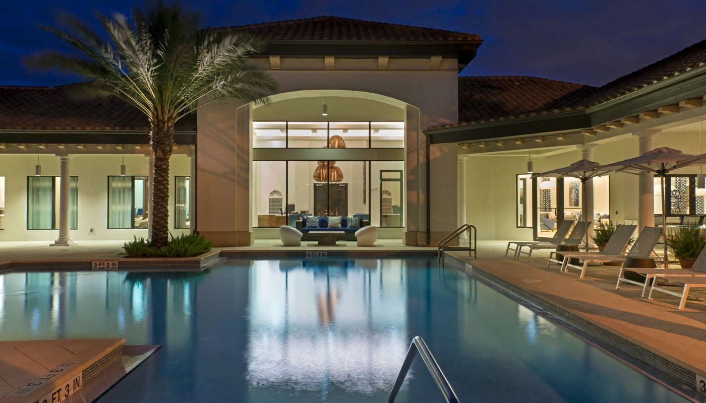 light house point resort style pool at night with palm trees, chaise lounge chairs, umbrella, social seating and a view of club house in the background - jefferson apartment group