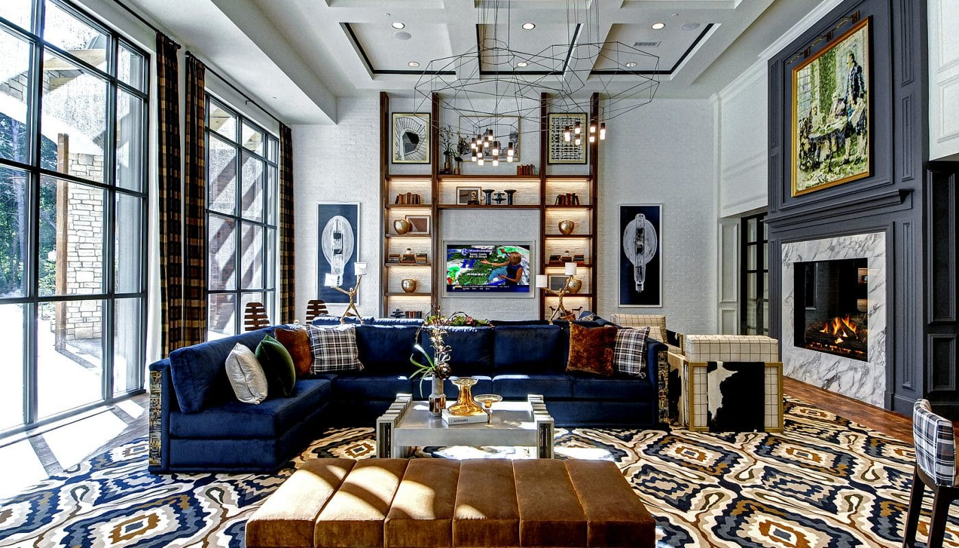 maybrook resident lounge with fireplace, social seating, cocktail tables, bookshelves, large windows and modern artwork - jefferson apartment group