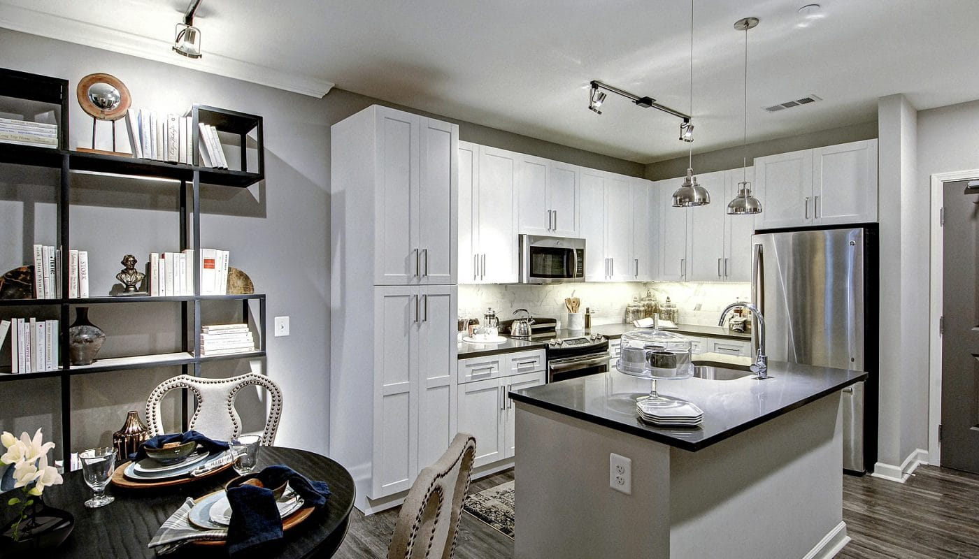 maybrook kitchen with white cabinetry, stainless steel appliances, island with quartz countertops and view of dining area with table, place settings and bookshelves - jefferson apartment group