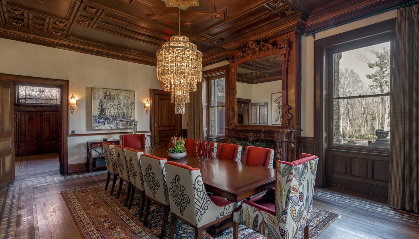 maybrook mansion dining area with large table, twelve chairs, chandelier, artwork, intricate mirror and large windows - jefferson apartment group