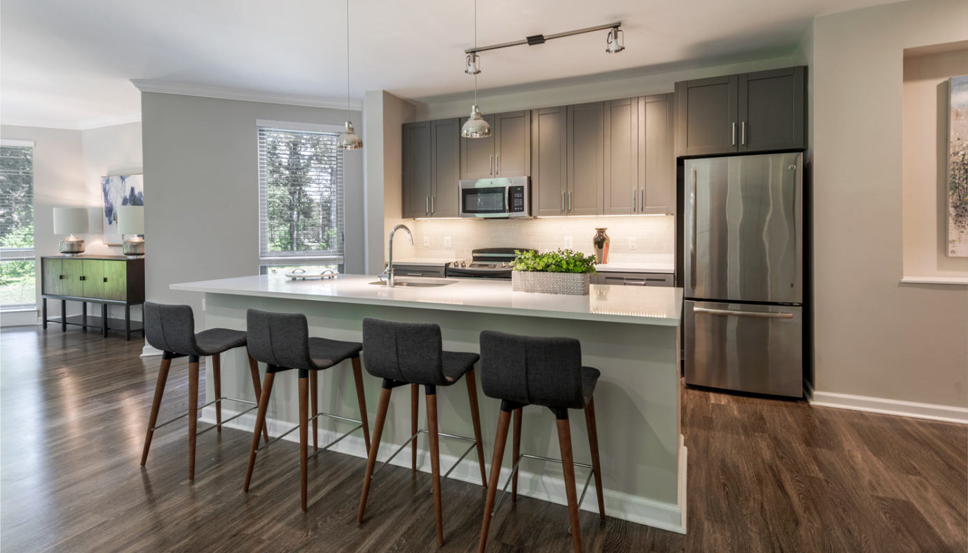 maybrook dining area with breakfast bar, four barstools, stainless steel appliances, quartz countertops and sleek plank flooring - jefferson apartment group