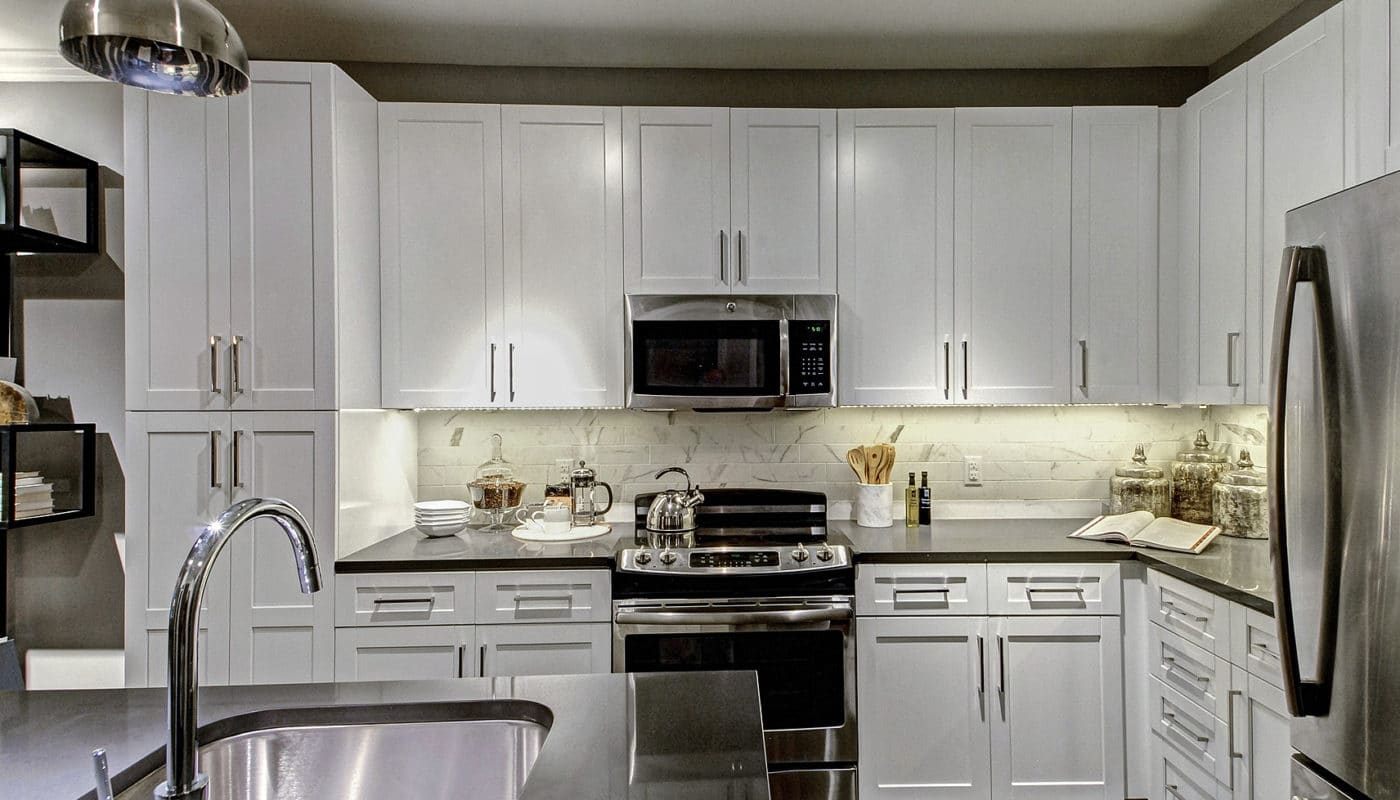 maybrook kitchen with quartz countertops, stainless steel appliances, white cabinetry and breakfast bar - jefferson apartment group