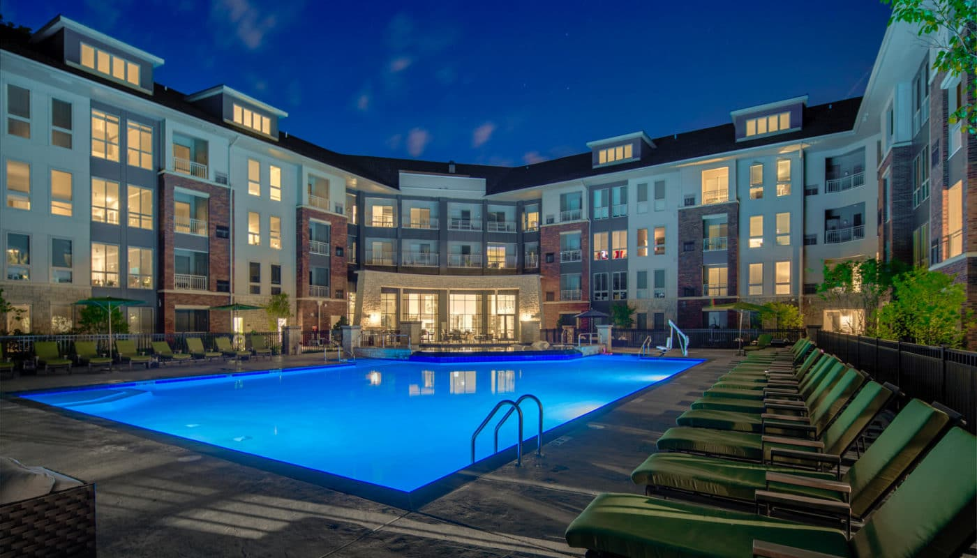 maybrook resort style pool with chaise lounge chairs, umbrellas, greenery, and view of apartment building in the background - jefferson apartment group