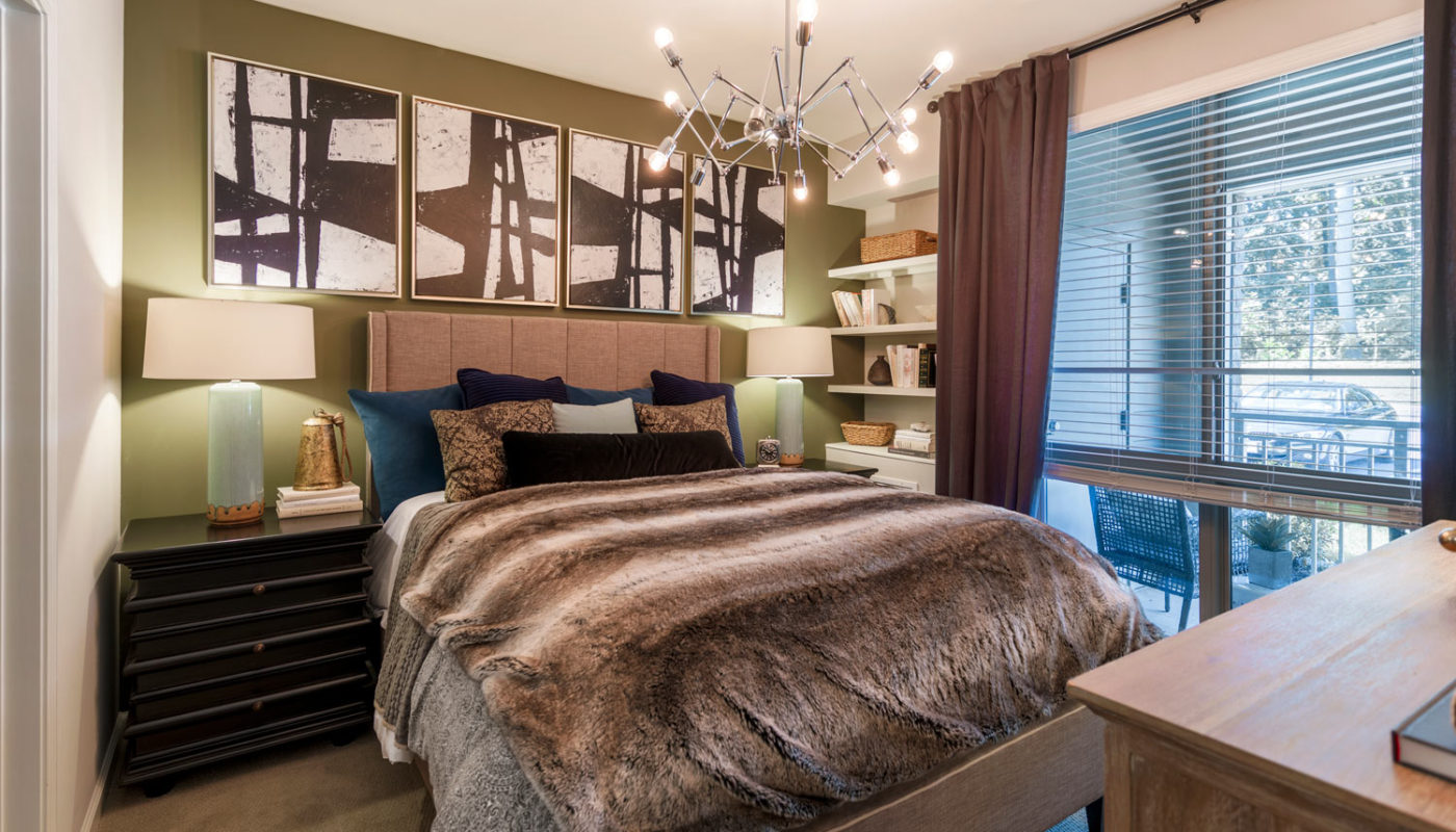 maybrook bedroom with bed, nightstands, bookshelf, dresser, modern artwork and view of balcony - jefferson apartment group