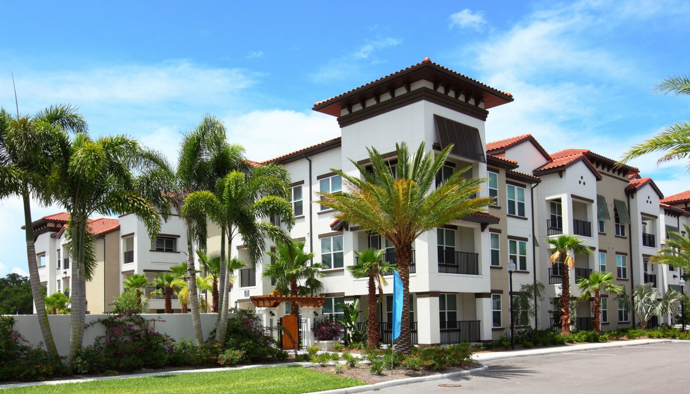 westshore exterior showing a three story building with balconies, palm trees and gated entrance - jefferson apartment group