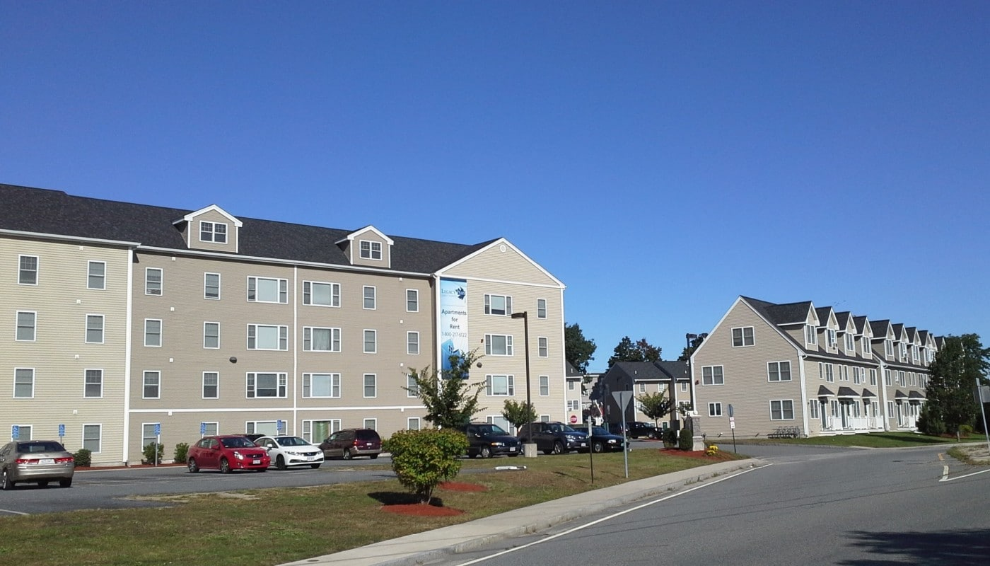 legacy park exterior showing four story apartment building and section of townhomes, landscaping and parking lot - jefferson apartment group