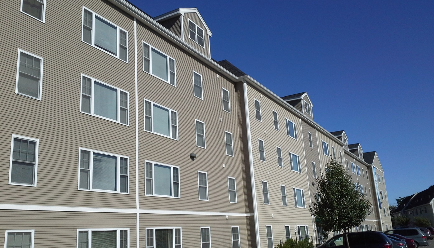legacy park exterior showing four story building, landscaping and parking lot - jefferson apartment group
