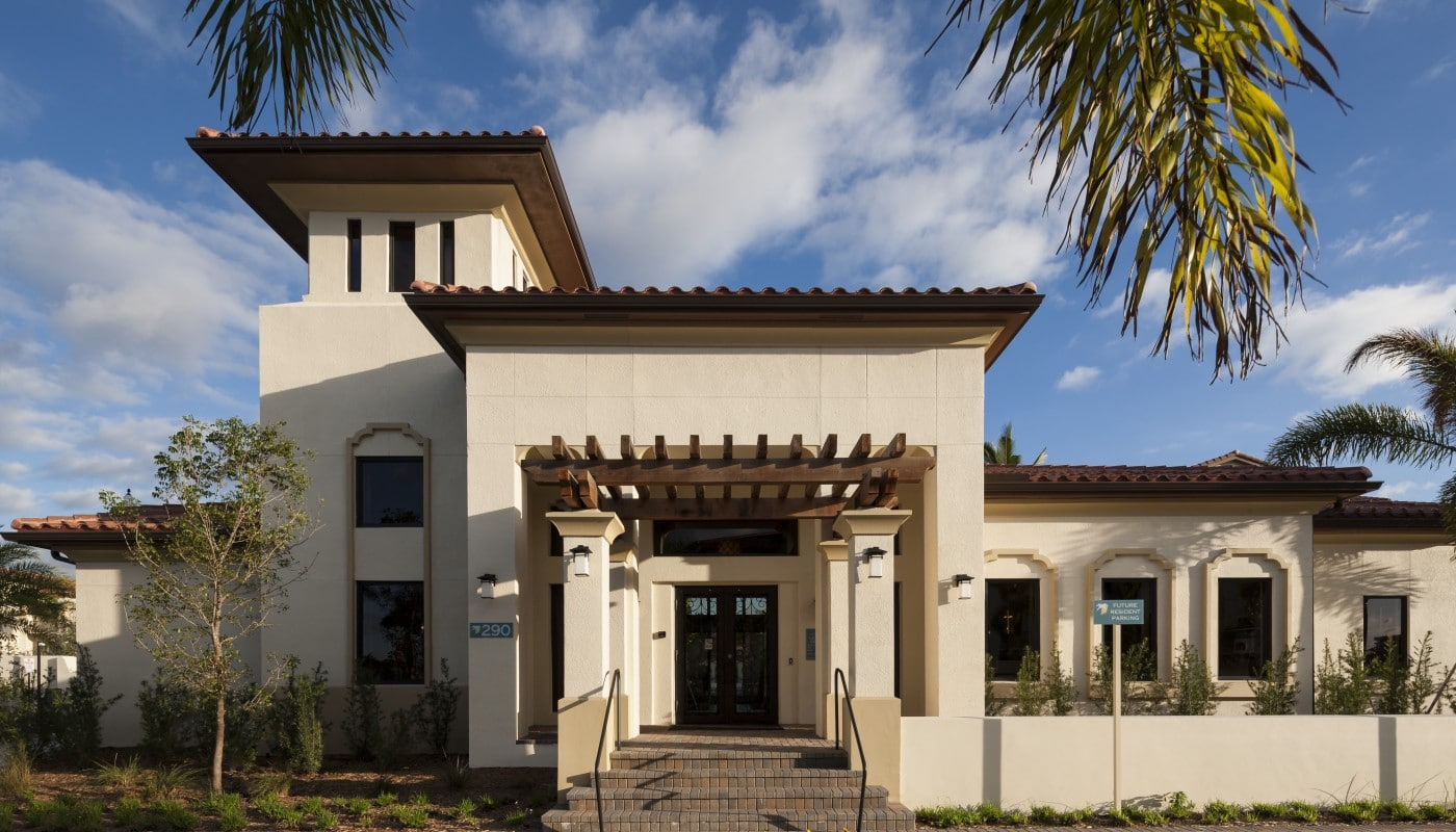 jefferson palm beach leasing office and resident lounge exterior with palm trees and lush landscaping - jefferson apartment group