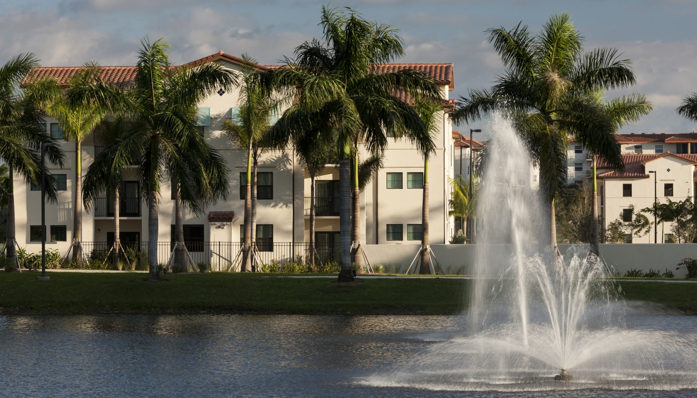 jefferson palm beach exterior showing a three story building with palm trees, a late and fountain - jefferson apartment group