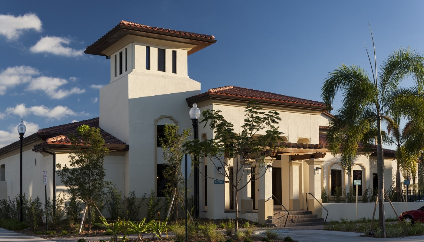 jefferson palm beach club house exterior with palm trees, landscaping and parking area - jefferson apartment group