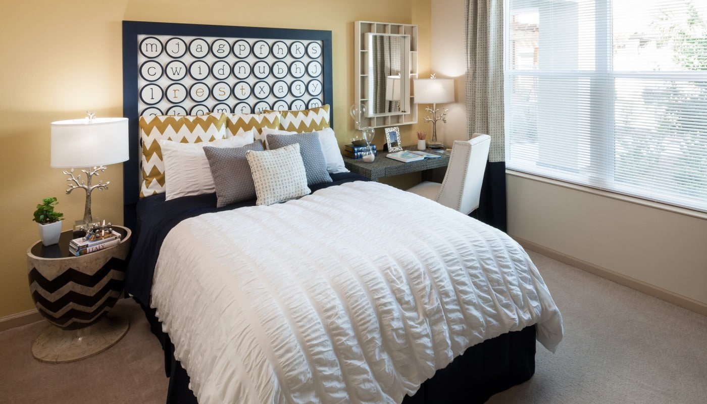 westshore bedroom with night stand, desk, large window and modern artwork - jefferson apartment group