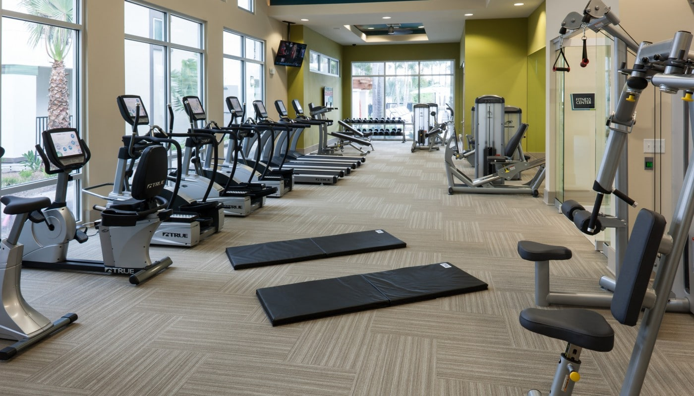 westshore fitness center with cardio equipment, strength training machines, flat screen tvs, large mirrors and large windows - jefferson apartment group