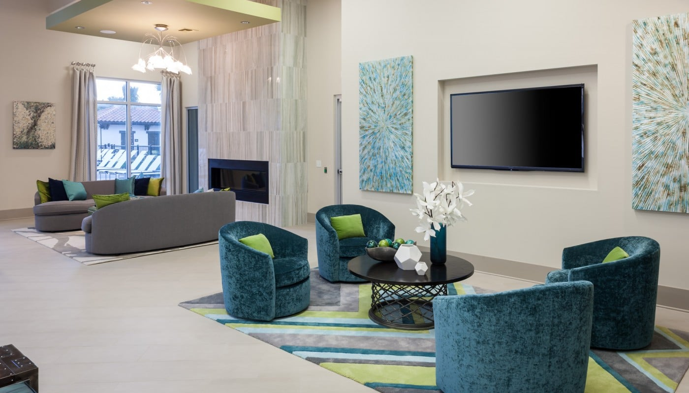 westshore resident lounge with fireplace, flatscreen tv, social seating and modern artwork - jefferson apartment group