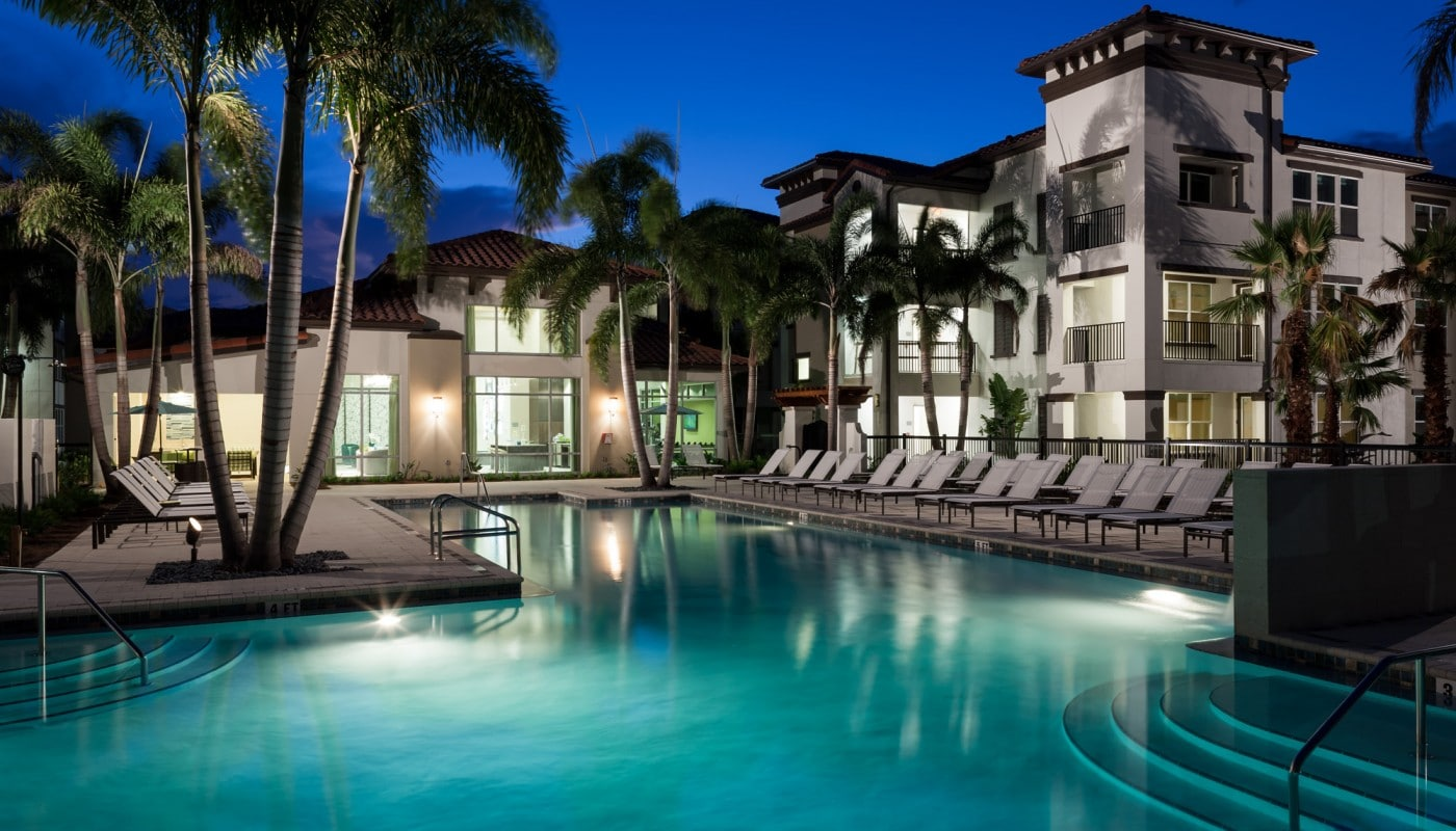 westshore resort style pool with chaise lounge chairs, palm trees and view of apartment building in the background - jefferson apartment group