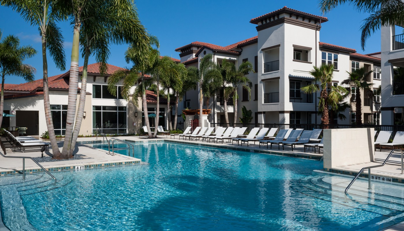 westshore resort style pool with chaise lounge chairs, pergola, palm trees and view of apartment building and wooded area in the background - jefferson apartment group