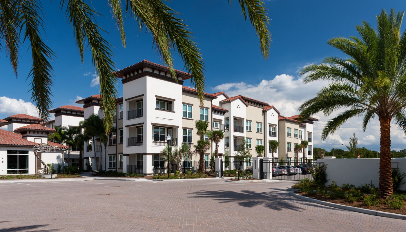 westshore exterior showing three story building with balconies, palm trees, and parking area - jefferson apartment group