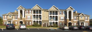 somerset park exterior showing three story building with stone accents, lush green lawn and large parking lot - jefferson apartment group