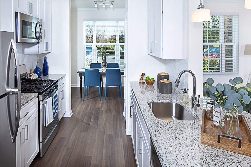 Kitchen with stainless steel appliances, gas stove, granite countertops, view of dining area and plank flooring at Jefferson somerset park luxury apartments in leesburg va