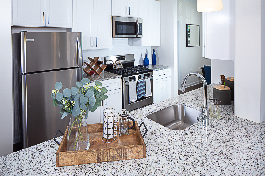 Kitchen with stainless steel appliances, gas stove, granite countertops and plank flooring at Jefferson somerset park luxury apartments in leesburg va