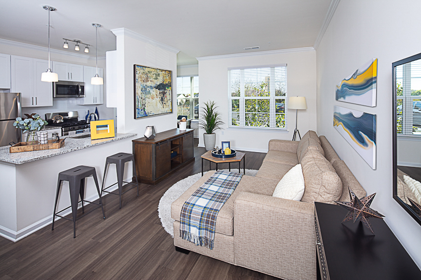 living space with sectional sofa, coffee table, end table, modern and view of kitchen with breakfast bar and barstools at Jefferson somerset park luxury apartments in leesburg va