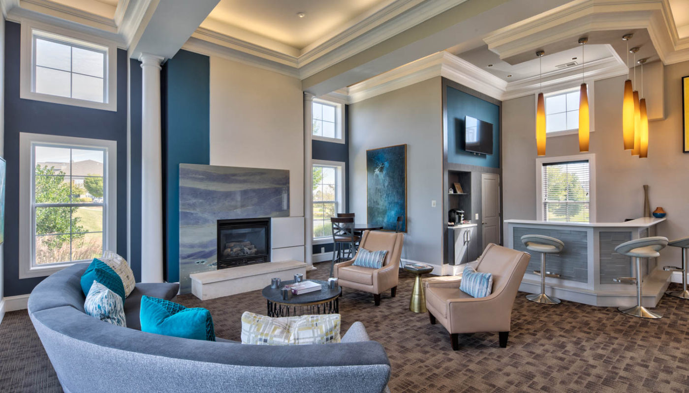 somerset park resident lounge with social seating, fireplace, bar seating, flat screen tv, large windows and modern lighting - jefferson apartment group