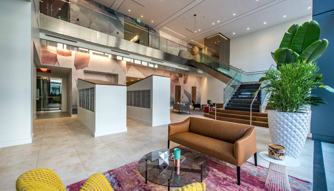 j malden center lobby with social seating, colorful rug, large indoor greenery, grand staircase and the mail center in the background - jefferson apartment group