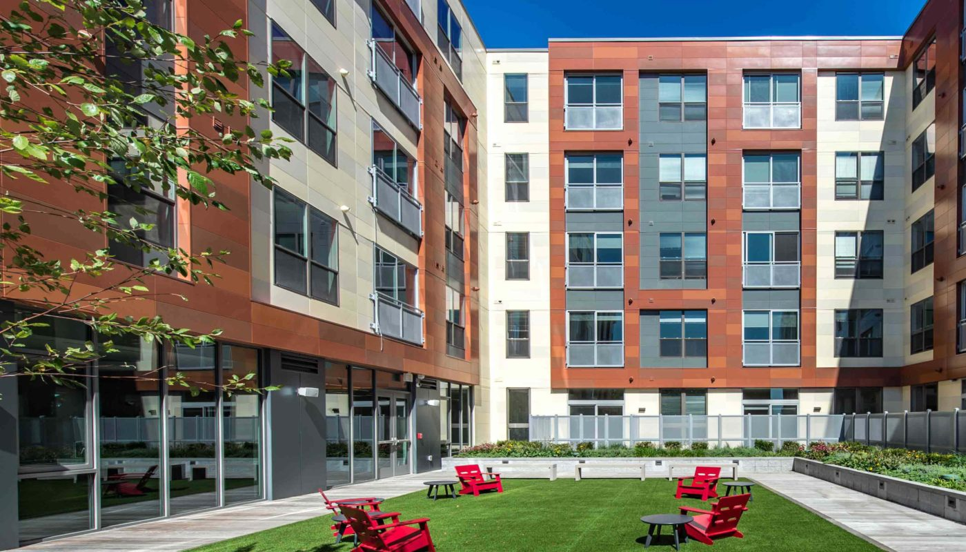 j malden center outdoor courtyard with lush lawn, bench seating and red Adirondack chairs - jefferson apartment group