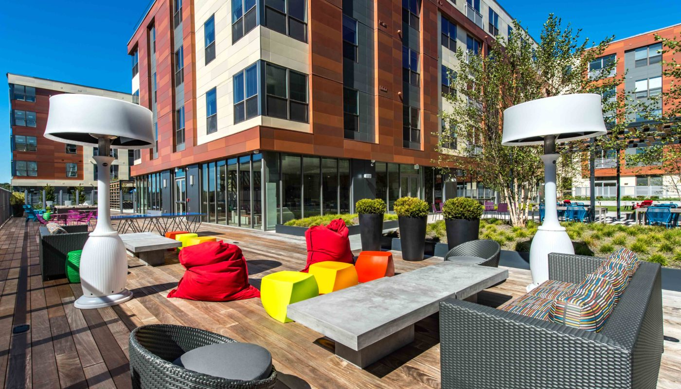 j malden outdoor courtyard with bean bag chairs, social seating, lush greenery and view of apartment building in the background - jefferson apartment group